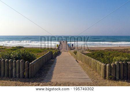 Wooden walkway through dune vegetation extending onto pier against beach ocean and blue sky coastal landscape in Durban South Africa