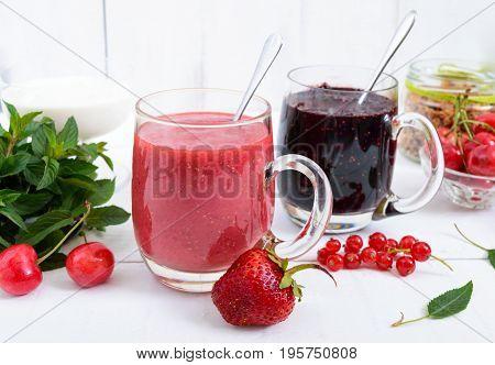 Berry smoothie in of glass cups yogurt granola fresh berries on white wooden background. Proper nutrition. Healthy breakfast. Dietary menu.