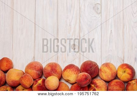 Ripe tasty peaches on a light wooden background. Selective focus.