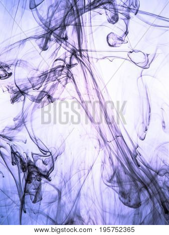 Ink swirl in a water on color background. The paint splash in the water. Soft dissemination a droplets of colored ink in water close-up. Abstract background. Explosion of color splashes acrylic ink.