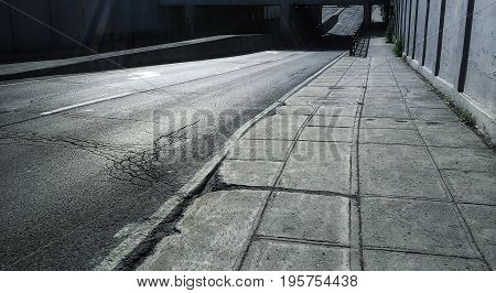 During a bright summer day. Some small and diffused light rays. Cracks on the asphalt of the street. Bridge. Concrete sidewalk.