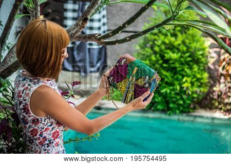 Summer portrait of a beautiful sexy girl with sunglasses and luxury handmade snakeskin python handbag in the swimming pool. Fashion outdoor. Tropical Bali island.