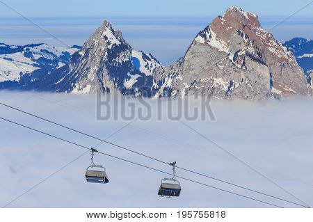 Chair lift on Mt. Fronalpstock in the Swiss canton of Schwyz summits of the Kleiner Mythen and Grosser Mythen mountains rising from sea of fog. The picture was taken in wintertime at the end of January.