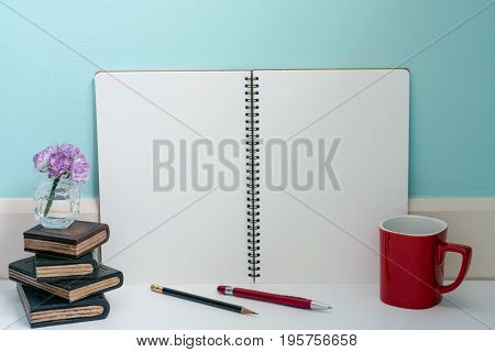 Red cup of coffee and wooden book with flower and blank page notebook pen and pencil relax business idea blue pastel wall background