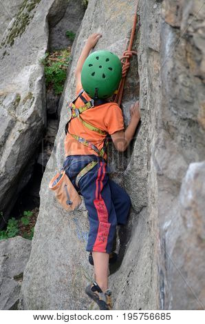 cliff-hanging, ascent of a mountain, the boy climbs the rock,	sport