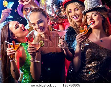 Dance party with group people dancing . Women and men have fun and drinking martini cocktail with citrus fruit in night club. Happy group people girls on foreground and disco ball on background.