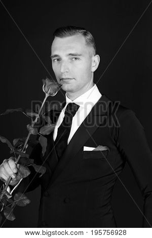 Business man with rose flower on black background valentines day romantic love concept