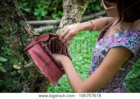 Young woman holding a luxury handmade snakeskin python handbag. Expensive clutch.
