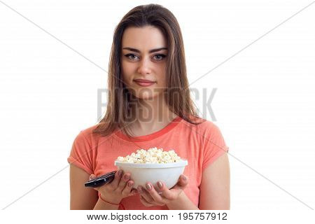 portrait of young brunette woman with tv remote and pop-corn in hands isolated on white background