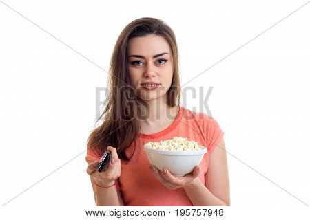 cutie young brunette woman with tv remote and pop-corn in hands isolated on white background