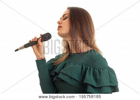 Sensual young girl in green dress sings song in microphone isolated on white background