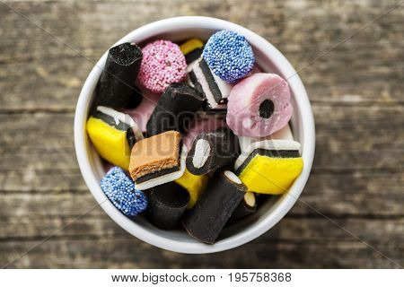 Mixed liquorice candies in bowl. Top view.