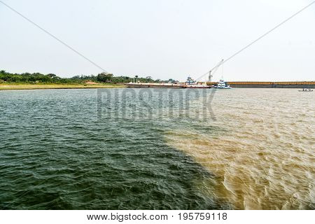 water meeting in brazil -amazon river with rio del negro clean and dirty river water with different streams