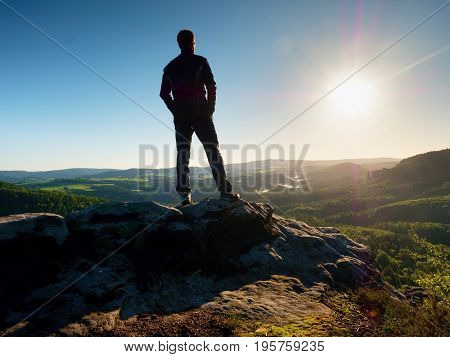 Man Stands On The Peak Of Sandstone Rock  Watching Over Valley To Sun. Beautiful Moment