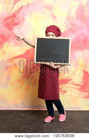 Small Girl Cook In Hat With Blackboard.
