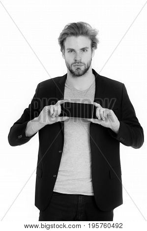 handsome bearded guy businessman or sexy man with beard and stylish hair using mobile or cell phone in black formal jacket isolated on white background business and communication black and white