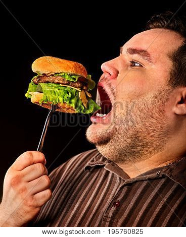Diet failure of fat man eating fast food hamberger. Overweight person who spoiled healthy food by eating hamburger on fork. Junk meal leads to obesity on dark background.