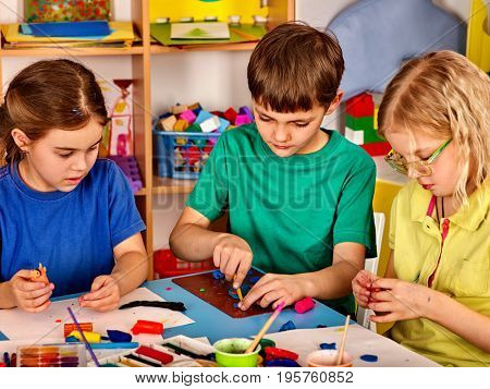 Small students painting in art school class. Children boy and girl drawing by paints on table. Portrait of kids in kindergarten. Children learn to be friends in team.