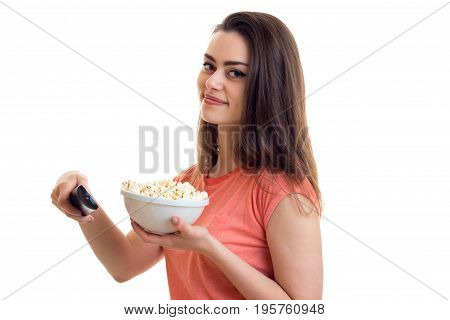 Cute young woman with tv remote and pop-corn watching movies isolated on white background