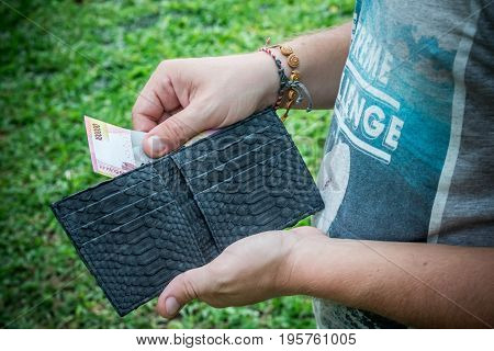 Snakeskin python leather wallet with money in male hands on green background. Asia.