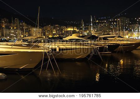Luxury yachts in Monaco Monte Carlo harbor at night with reflection in water. France