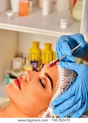 Filler injection for woman forehead face. Plastic aesthetic facial surgery by doctor in beauty clinic. Removing wrinkles with help of new technologies. Restoration of facial skin.