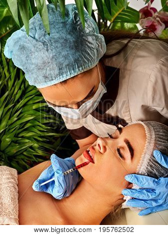 Filler injection for female face. Plastic aesthetic facial surgery by doctor in beauty clinic. Young woman giving injections. Waterfall and green plants in background.