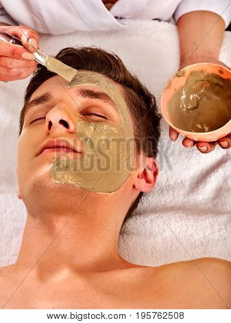 Mud facial mask of man in spa salon. Massage with clay full face. Girl on with therapy room. Beautician with bowl therapeutic procedure isolated background. Mask made of healing clay, close-up.