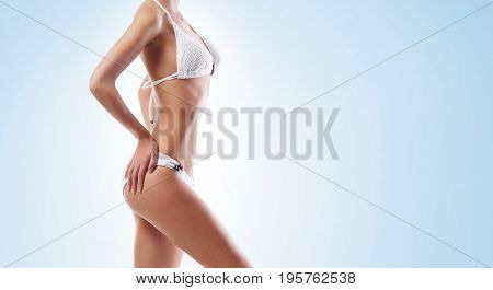 Fit body of a beautiful and young woman. Health, sport, fitness, nutrition, weight loss, diet, cellulite removal, liposuction, healthy life-style concept.