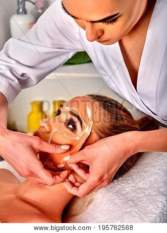 Collagen face mask . Facial skin treatment. Face of woman receiving cosmetic procedure in beauty salon close up number one isolated. Beautician removes mask. Removal of skin defects.