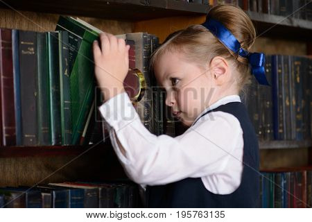 Cute little girl looking for a book in the old library. Educational concept.