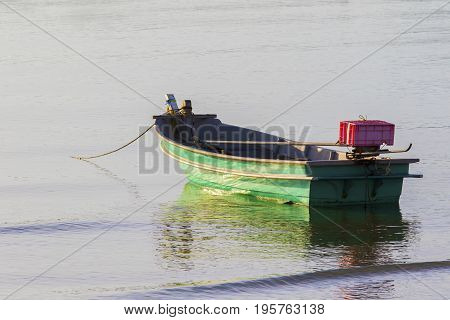 lonely metal boat floating on sea beach