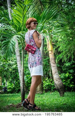 Outdoor fashion portrait of glamour sensual young stylish lady in sunglasses with luxury handmade snakeskin python bag. Python handbag. Sunny day, green plants, tropical palms.