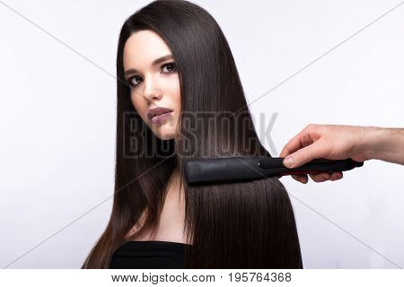 Beautiful brunette girl with a perfectly smooth hair, curling and classic make-up. Beauty face. Picture taken in the studio on a white background.