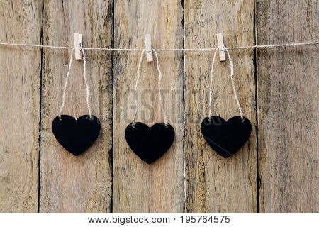 Three Heart Shape Blackboards Hanging On Clothespin On String Against Rustic Wood Background