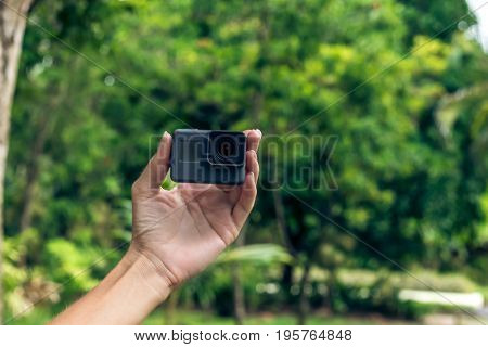 Young woman hand holding extreme action camera in the asian green park.
