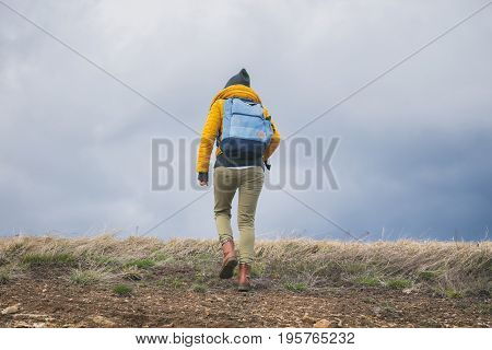 Hiker - girl walking up the steep hill.