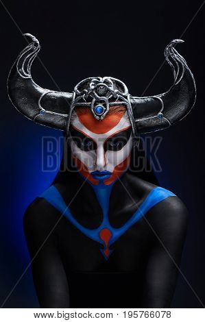Mystery portrait of female faun with blue eyes body art and silver snakes on black horns