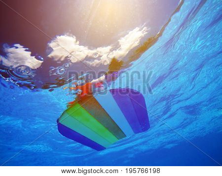 Rainbow pattern styrofoam swimming board or baseboard floating in swimming pool water summertime vacation recreational activity object in the poolside underwater view