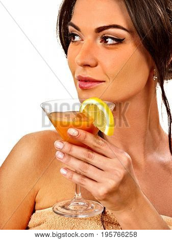 Girl drinking fruit cocktail on summer party. Woman with fresh fruits hairstyle and bare back hold halves of grapefruit with cocktail umbrella. Female enjoys citrus. Girl is resting abroad.