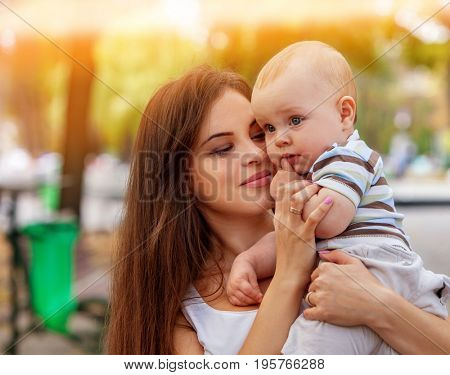 Baby in park outdoor. Kid on mom's hands. Happy beautiful mom and child summer on city outside. Portrait of happy loving mother and her son spring outdoors . Color tone on shiny sunlight background.