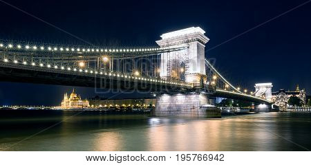 Famous Chain bridge Hungarian parliament building at night and river Danube in Budapest