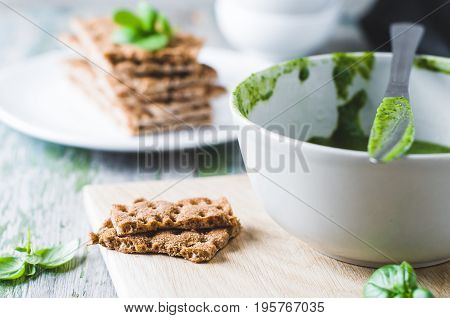 Crispbread And Green Salsa On The Old Wooden Table