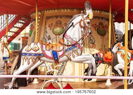 Horses on a carnival Merry Go Round. Old French carousel in a holiday park. Big roundabout at fair in amusement park