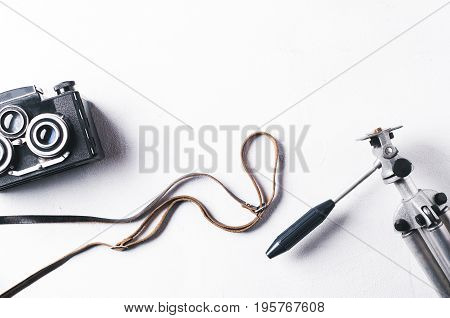 Old Camera And Tripod On A White Concrete Background. Vintage Item, Top View And Flat Lay