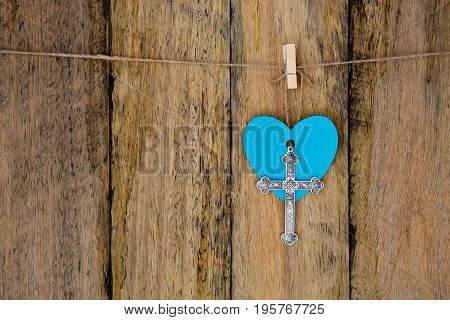Silver Metal Crucifix Hanging With A Blue Heart On String Against Rustic Wooden Background