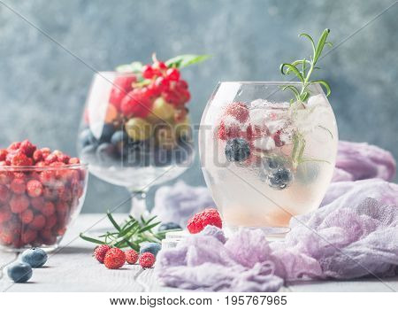 Detox fruit infused flavored water with ice. Refreshing summer homemade cocktail with berries