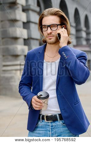 Young businessman walking down the street and talking on his smartphone. Lively active lifestyle.