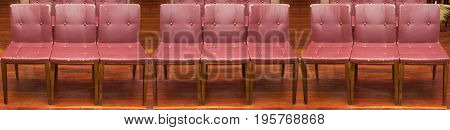 Old red leather chairs in a row.