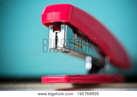 The red stapler isolated from the blue background.